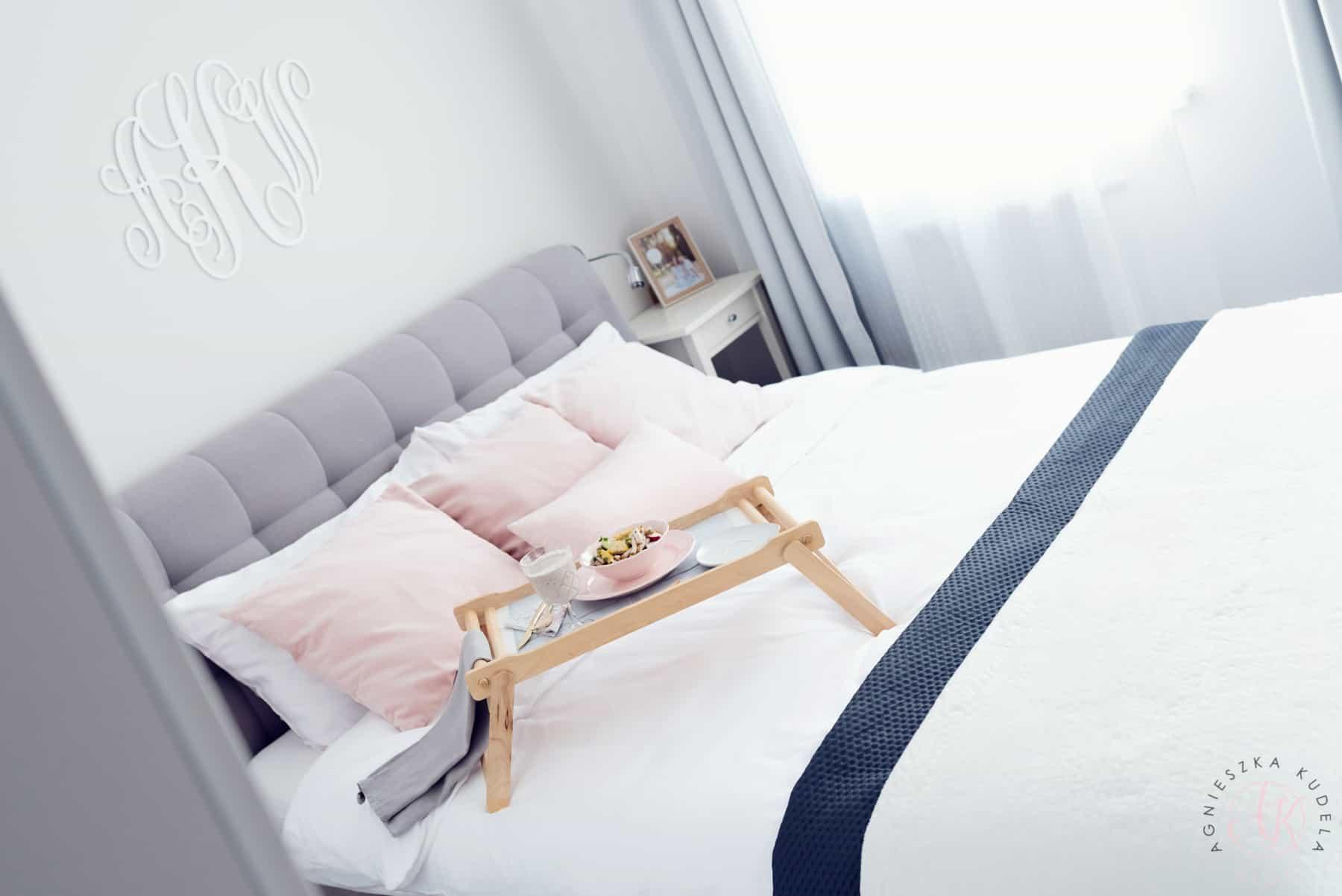 Szara sypialnia, biała pościel, różowe poduszki, śniadanie do łóżka