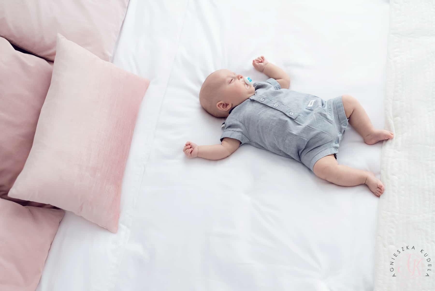 Niemowlę, biała pościel, różowe poduszki