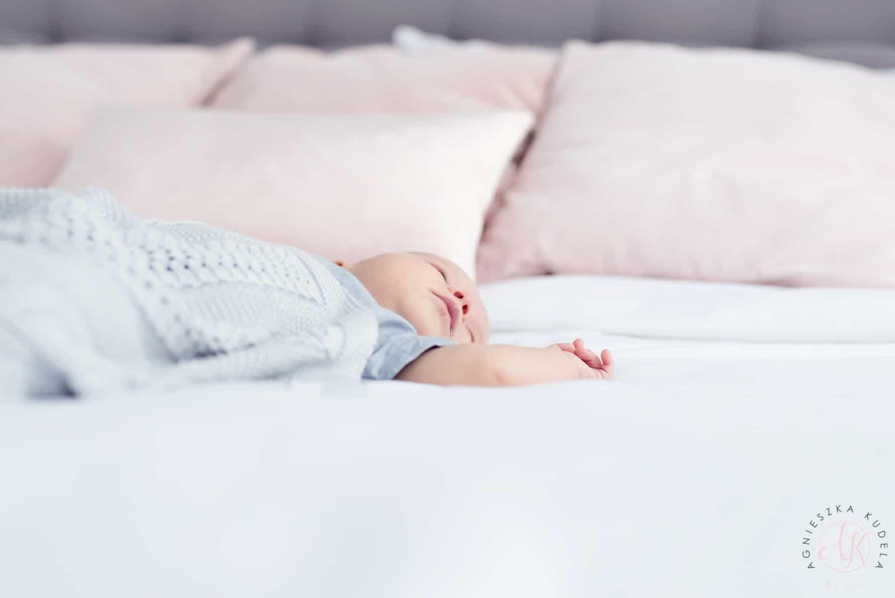 Śpiące niemowlę, biała pościel
