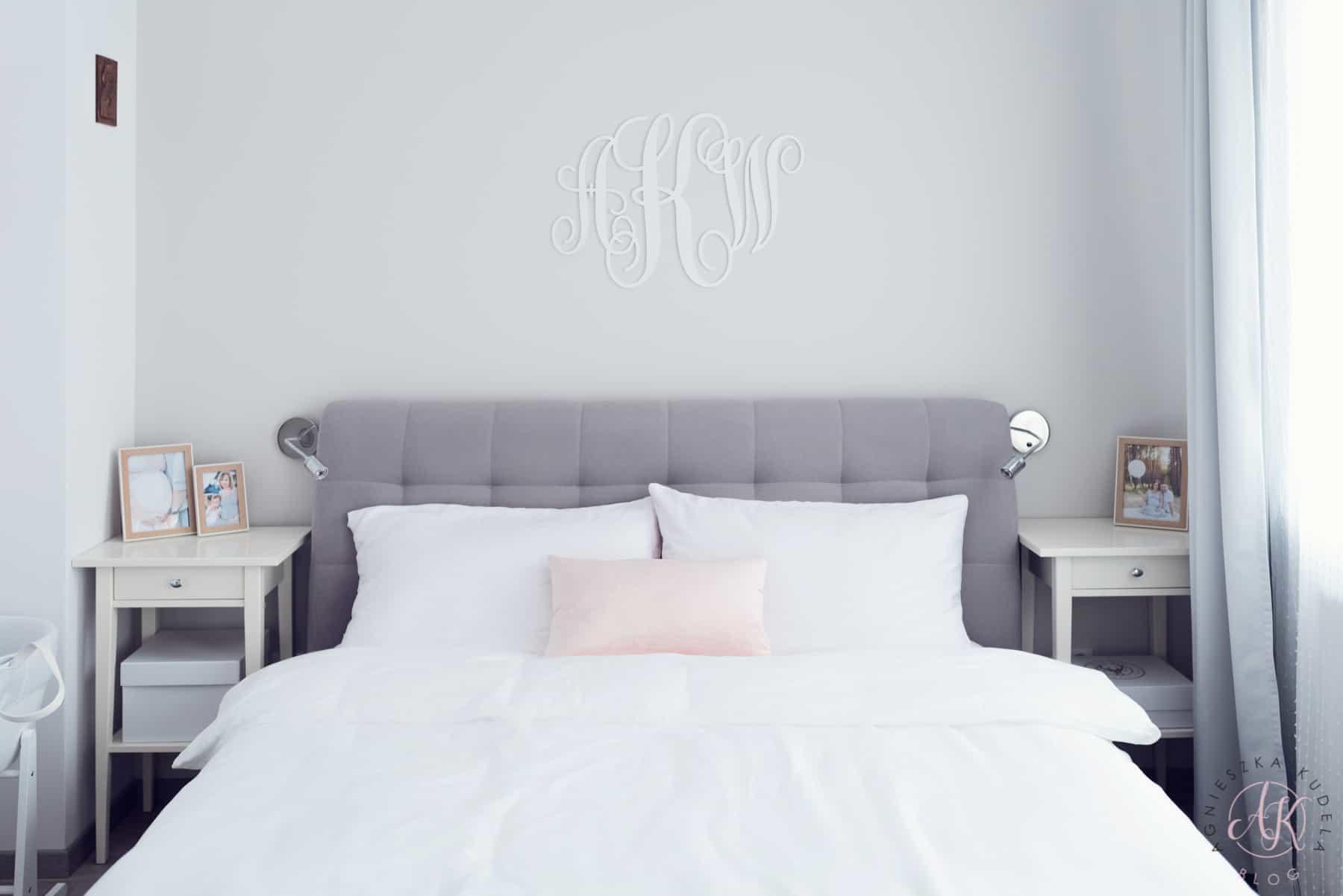 Biała pościel w sypialni, różowe poduszki, stoliki nocne, kinkiety, monogram